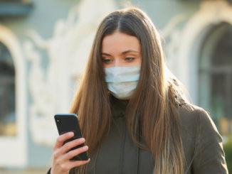 Eine junge Frau mit Schutzmaske und Smartphone. (Symbolbild) - Raman Tyukin/Shutterstock.com