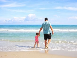 Symbolbild: Urlaub - Kind mit Vater am Strand